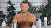 bez košile muž ukazuje prsty při pohledu na kameru v blízkosti zelených rostlin na rozmazaném pozadí v koupelně