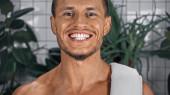 boldog férfi bemutató fehér fogak, miközben mosolygott a fürdőszobában növények közelében elmosódott háttér