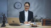Mosolygó biztosítási ügynök gazdaság toll mellett notebook, laptop és mérlegek az asztalon