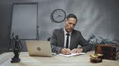 Biztosítási ügynök öltöny írás notebook közelében laptop, könyvek és mérlegek az asztalon