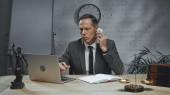 Biztosítási ügynök beszél okostelefon közelében laptop, notebook és szobor az igazságszolgáltatás