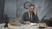 Biztosítási ügynök beszél okostelefon közelében laptop, notebook és mérlegek az asztalon az irodában