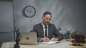 Biztosítási ügynök írás notebook, miközben dolgozik közelében eszközök és mérlegek