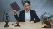 Biztosítási ügynök gazdaság könyv, miközben néz kamera közelében kalapács, szobor az igazság és mérlegek az asztalon
