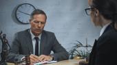 Biztosítási ügynök írás notebook közel mérlegek, kalapács és kolléga homályos előtérben az irodában