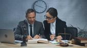 Mosolygó biztosítási ügynök olvasókönyv mellett kolléga toll és laptop az asztalon
