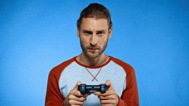KYIV, UKRAINE - NOVEMBER 24, 2020: bearded man holding joystick and playing video game on blue stock vector