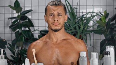 sad shirtless man near green plants on blurred background in bathroom