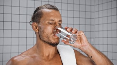 Shirtless man drinking water while holding glass in bathroom stock vector