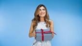 kíváncsi nő kezében csomagolva ajándék doboz és mosolygós kék