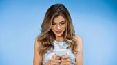 usmívající se žena s kudrnatými vlasy smskování na smartphone na modré
