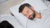 vousatý muž spí na bílém lůžku doma