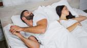 muž s mobilním telefonem při pohledu na přítelkyni spí v blízkosti v posteli