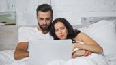 mladý pár s úsměvem při sledování filmu na notebooku v posteli