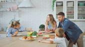 Rodiče a děti stojící v blízkosti croissantů a banánů v kuchyni