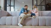 Férj beszél feleséggel a kanapén otthon