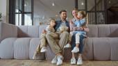 Usmívající se rodina s popcornem sedí na gauči