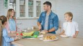 Veselá rodina stojící v blízkosti pečiva a zeleniny v kuchyni