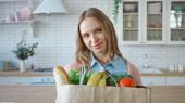 Nő étellel papírzacskóban nézi kamera a konyhában
