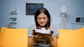 Fiatal nő kezében ízletes torta csukott szemmel a nappaliban