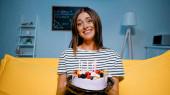 Veselá žena drží narozeninový dort a dívá se do kamery v obývacím pokoji