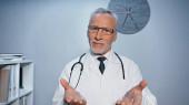 Usmívající se lékař ukazuje s rukama na fotoaparát na rozmazané popředí v nemocnici