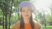 glückliche stilvolle Frau lächelt in die Kamera im sonnigen Herbstpark