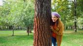 izgatott nő nézi kamera, miközben bujkál fa törzs a parkban