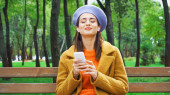 pleased woman in stylish autumn clothes listening music in park