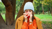 young woman in autumn outfit enjoying aroma of ripe apple in park