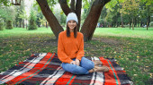 happy stylish woman smiling at camera while sitting on plaid blanket in park