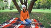 radostná žena se usmívá na kameru, zatímco odpočívá na kostkované přikrývce v podzimním parku