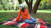 young trendy woman looking away while resting on checkered blanket in park