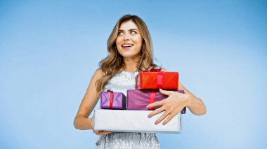 Happy woman with curly hair holding wrapped presents on blue stock vector