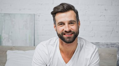 Young bearded man smiling while looking at camera in bedroom stock vector