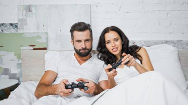 KYIV, UKRAINE - JANUARY 26, 2021: concentrated man and woman gaming with joysticks in bed stock vector