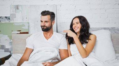 Joyful brunette woman pointing at discouraged boyfriend in bedroom stock vector