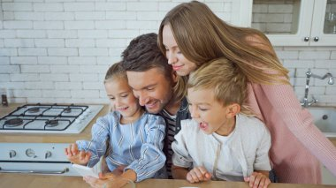 Cheerful family with kids using smartphone in kitchen stock vector