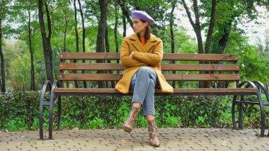 Parkta bankta çapraz kollarla otururken bakışlarını kaçıran modaya uygun bir kadın.