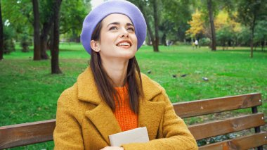 Cheerful woman in beret looking up while sitting with book in park stock vector