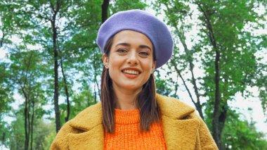 Joyful trendy woman smiling at camera in autumn park stock vector