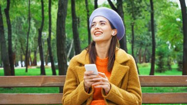 joyful woman with smartphone looking away while listening music in autumn park