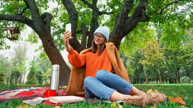 Smiling woman in stylish autumn outfit taking selfie on mobile phone during picnic in park stock vector