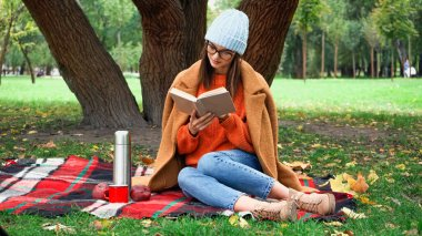 Stylish woman in autumn clothes reading novel during picnic in park stock vector