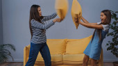 happy mother and excited daughter pillow fighting in living room