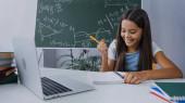 boldog lány kezében toll és nézi jegyzettömb mellett laptop az asztalon