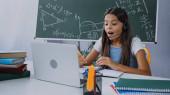 aufgeregtes Kind im Headset schaut auf Laptop, während es zu Hause online lernt