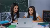 boldog anya és lánya néz laptop közelében notebook az asztalon