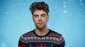 Muž ve svetru při pohledu na kameru pod padajícím sněhem na modrém pozadí