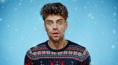 vzrušený muž v teplém svetru při pohledu na kameru pod padajícím sněhem na modrém pozadí